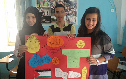 A photo of some Palestinian children holding a picture they have prepared of UK sites